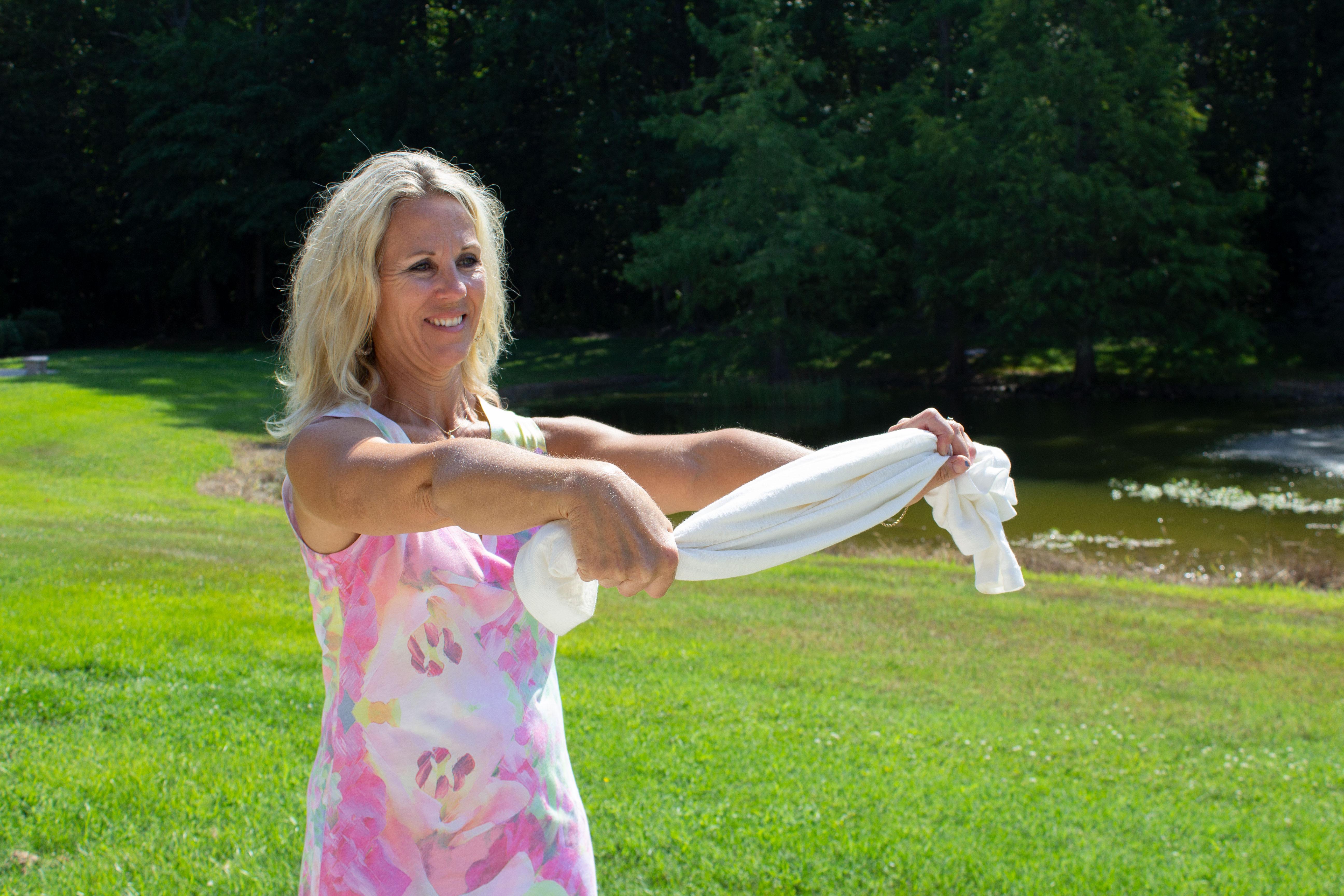 woman stretching by twisting towel