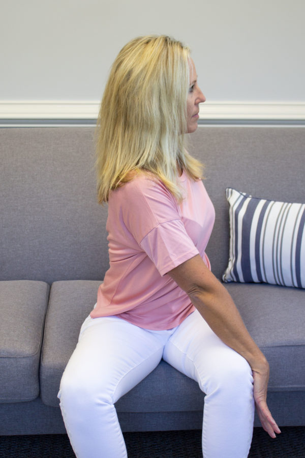 woman stretching by twisting dumbbell