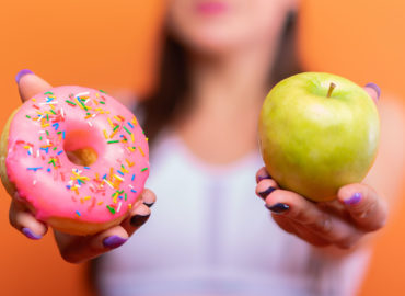Woman holds up an apple and donut
