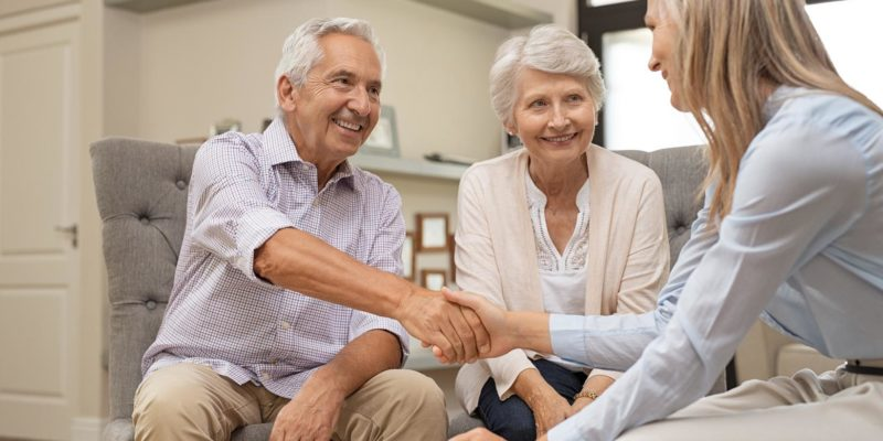 elderly couple shaking hands iwth young woman